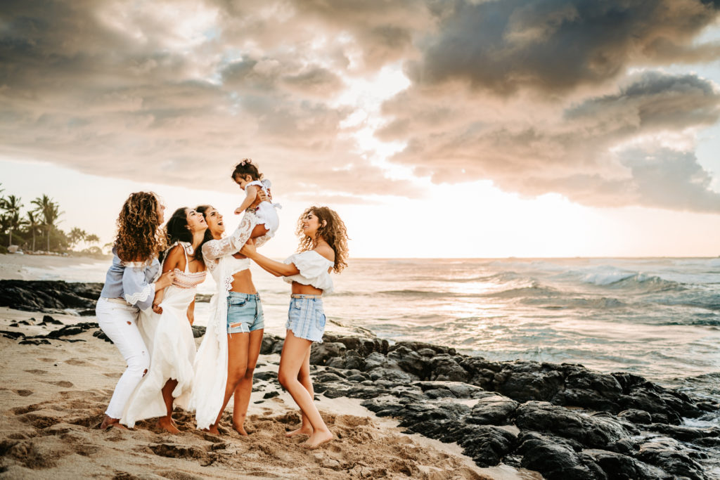 Family Photography, a woman stands with her four daughters, three teens, and a baby girl. They are on the beach near the ocean.