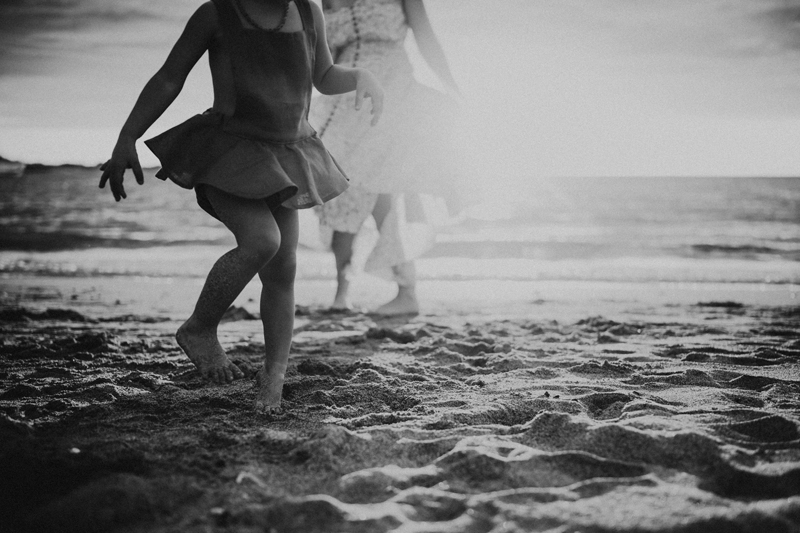 Family Photographer, a couple of girls in swimsuit dresses run through the sand at the beach