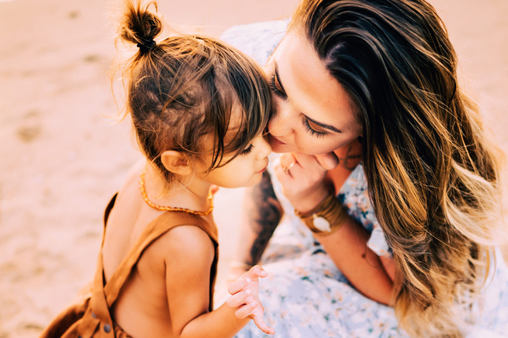 Family Photography, a little girl leans into her mother, face to face at the beach