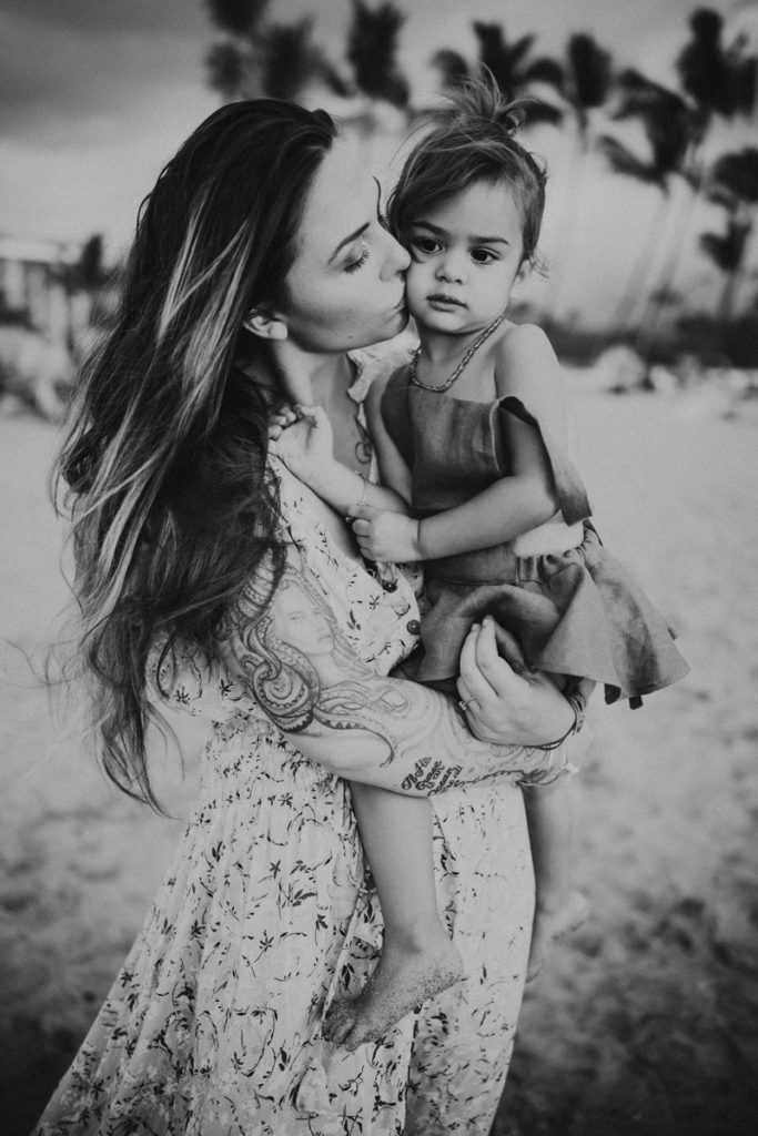 Family Photography, A mother kisses young daughter on the cheek as she holds her. they are outdoors.