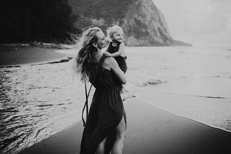 Family Photographer, A woman in a dress holds young child as she walks near the ocean