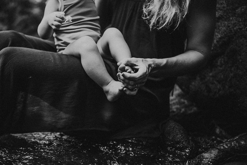 Family Photographer, a small child sits on moms lap, she holds the toddlers toes, motherhood